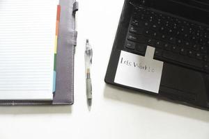 scrivania da ufficio bianca vista dall'alto con laptop e notebook foto