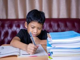 ragazzo che fa i compiti e legge su un tavolo di legno. foto