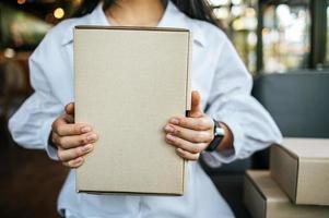 donna che tiene una cassetta dei pacchi al bar foto