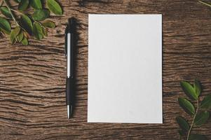una carta bianca e una penna sono posizionate su legno. foto