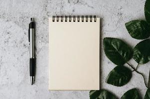 taccuino, penna e foglia sono posizionati su sfondo bianco foto