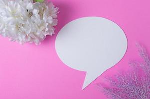 simboli vocali fatti di carta e fiori posti su uno sfondo rosa. foto