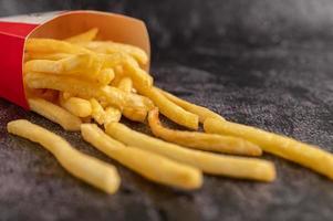 patatine fritte versate da un sacchetto su un pavimento di cemento nero. foto