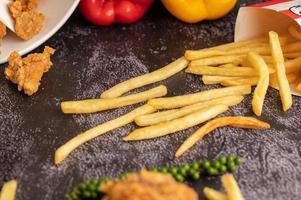 pollo fritto e patatine fritte sul pavimento di cemento nero. foto