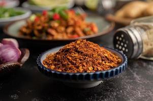 pepe di cayenna su un piatto su cemento nero, fuoco selettivo. foto