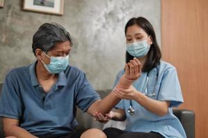 terapia fisica medico femminile su pazienti maschi anziani. foto