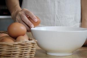 cuoca in un grembiule bianco sta rompendo un uovo nella cucina di casa. foto