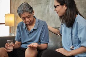 assistenza sanitaria domiciliare, dottoressa che aiuta il paziente maschio a prendere medicine foto