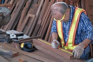 vecchio falegname asiatico che lavora in una fabbrica di falegnameria. foto