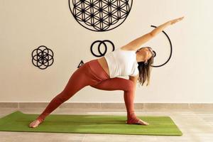 giovane modello femminile che esegue asana yoga presso lo studio di yoga foto
