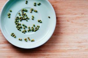 fagioli verdi secchi sparsi sul piattino, vista dall'alto foto