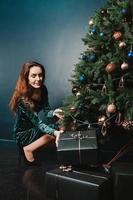 bella femmina con scatole regalo vicino all'albero di natale foto