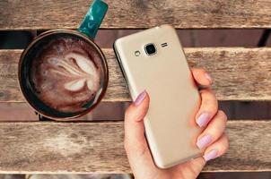mano femminile che tiene lo smartphone al bar, con cappuccino sul tavolo foto