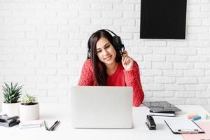 giovane donna latina in cuffie nere che insegna inglese online foto