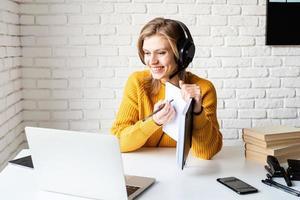 giovane donna in cuffie nere che studia online utilizzando laptop foto