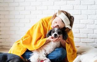 divertente giovane donna in plaid giallo seduta con i suoi cani a leggere un libro foto