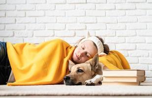 divertente giovane donna in plaid giallo che dorme con il suo cane foto