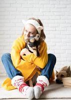 divertente giovane donna in plaid giallo seduta sul pavimento che abbraccia il suo cane foto