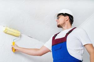 giovane uomo in tuta blu e elmetto bianco dipinto muro foto