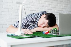 giovane stanco che dorme sulla sua scrivania. manichino del progetto di energia rinnovabile foto