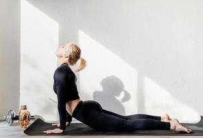 giovane donna atletica che si allena o fa yoga stretching a casa foto