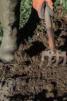 l'agricoltore prepara la terra per la semina con lo strumento dell'aratro in primavera. foto