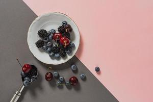 mirtilli, more, ciliegie su piatto e cucchiaio da gelato foto