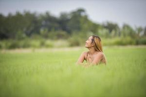 giovane donna seduta sentirsi bene nel campo in erba. foto