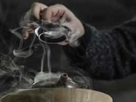 la mano maschile ravvicinata apre il coperchio di una teiera di argilla foto