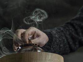 la mano maschio ravvicinata ha chiuso il coperchio di una teiera di argilla fatta di argilla yixing foto