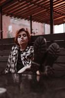 la giovane donna con i capelli rossi corti in un bar ha messo le gambe sul tavolo foto