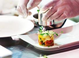 chef che cucina, chef che prepara il cibo, chef che decora il piatto in cucina foto