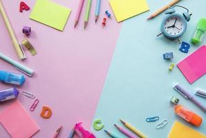cornice di diversi articoli di cancelleria su sfondo rosa e blu foto