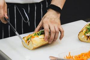 lo chef prepara il panino in cucina foto