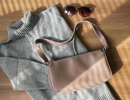 piccola borsa in pelle beige e maglione grigio da donna foto