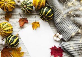foglie di acero di autunno, zucche e sciarpa di lana su un fondo di legno. foto