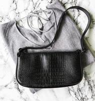piccola borsa in pelle nera e maglione grigio da donna foto