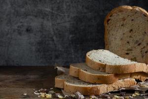 pane integrale di grano affettato su fondo di legno rustico scuro foto