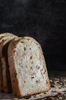 pane integrale di grano affettato del primo piano su fondo scuro foto
