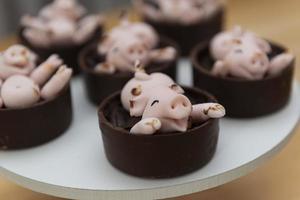 caramelle di maialini rosa carini felici che giocano nel fango foto