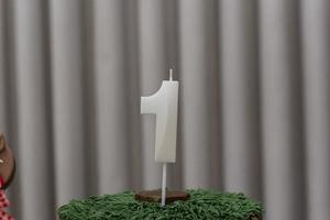 candela a forma di numero uno infilzata nella glassa di torta al cioccolato. foto