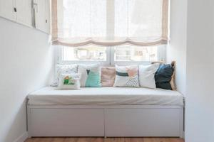 bellissimo spazio accogliente in stile nordico. divano con cuscini. foto