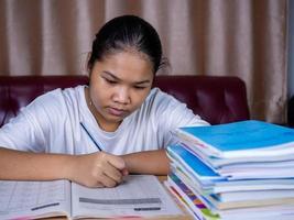 ragazza che fa i compiti su un tavolo di legno e c'era una pila di libri. foto