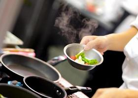 chef che prepara cibo, pasto, in cucina, chef che cucina foto