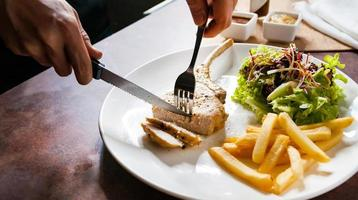 bistecca di braciola di maiale con insalata e patatine fritte foto