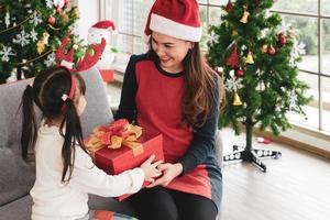 la madre asiatica e il bambino aprono insieme la scatola del regalo di natale foto