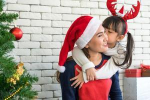 la madre e il bambino asiatici celebrano insieme il festival di natale foto
