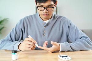 l'uomo usa la lancetta sul dito per controllare il livello di zucchero nel sangue con il glucometro foto