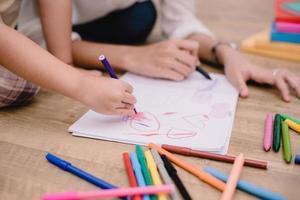 mani chiuse della mamma che insegna ai bambini piccoli a disegnare cartoni animati foto