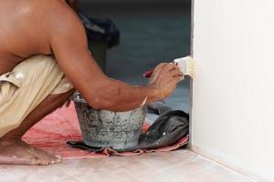 primo piano del pittore che dipinge il muro con il pennello foto